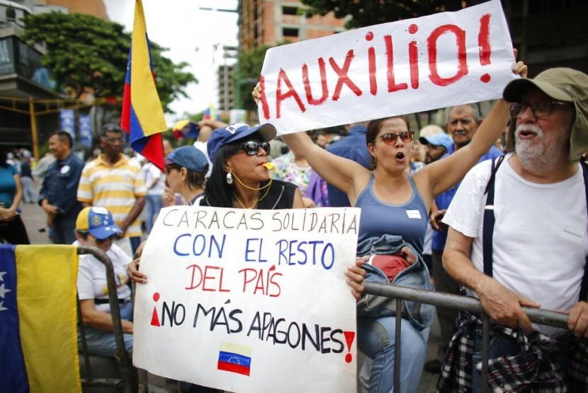 Warga Venezuela memprotes pemadaman listrik besar-besaran saat kampanye bersama pemimpin oposisi Juan Guaido di Caracas, Venezuela, Selasa (23/7).