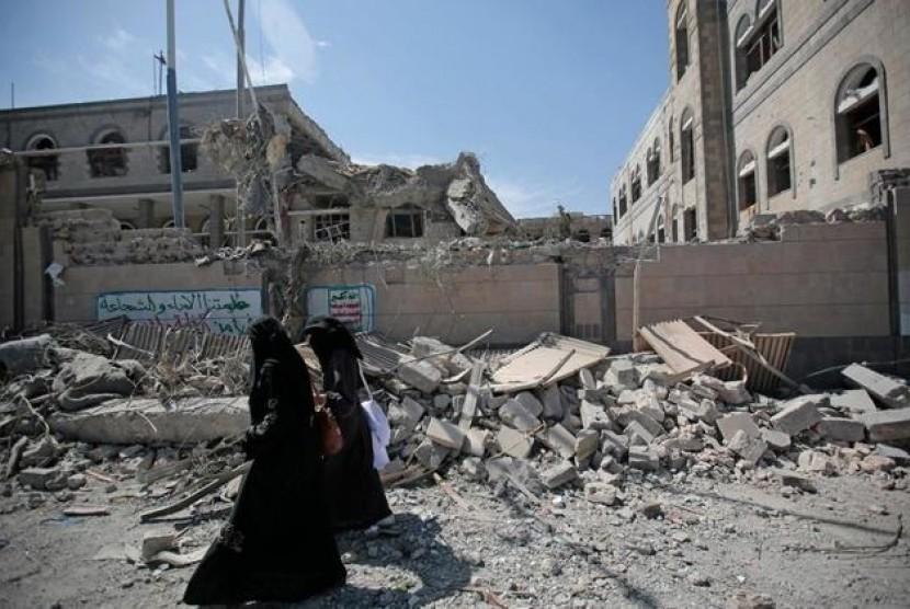 Warga Yaman berjalan di antara runtuhan puing gedung yang hancur terkena serangan udara di Sanaa, Yaman, 7 Mei 2018.