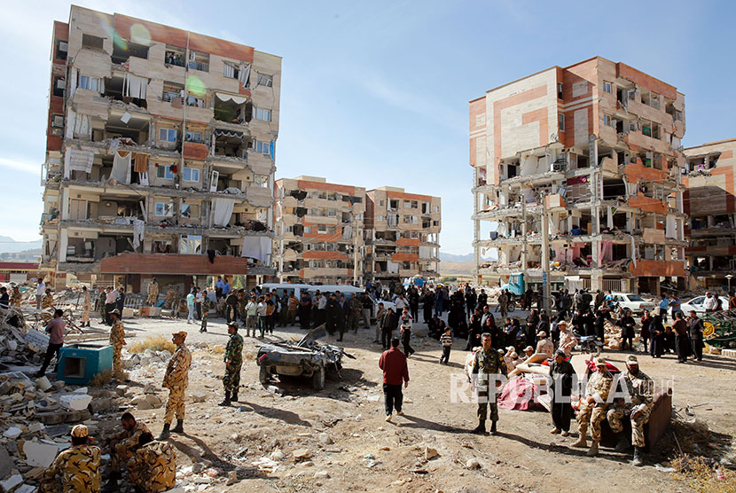 Warga yang selamat berkumpul di sekitar reruntuhan bangunan yang hancur akibat gempa di kota Sarpol-e-Zahab di Provinsi Kermanshah, Iran, Senin (13/11).
