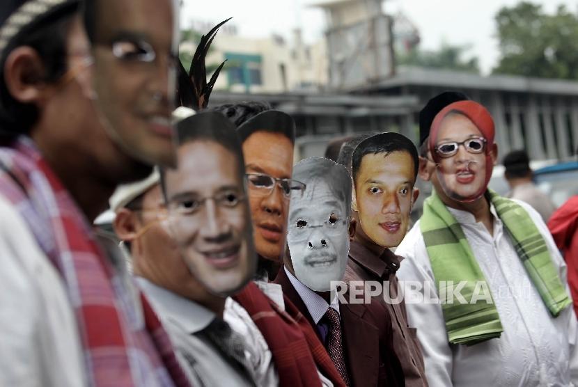 Warga yang tergabung dalam kelompok Bangga Jakarta melakukan aksi damai menggunakan topeng pasangan calon gubernur DKI Jakarta saat menyampaikan Petisi Pilkada Damai di depan Kantor KPU DKI Jakarta,Jakarta Pusat, Kamis (13/10).