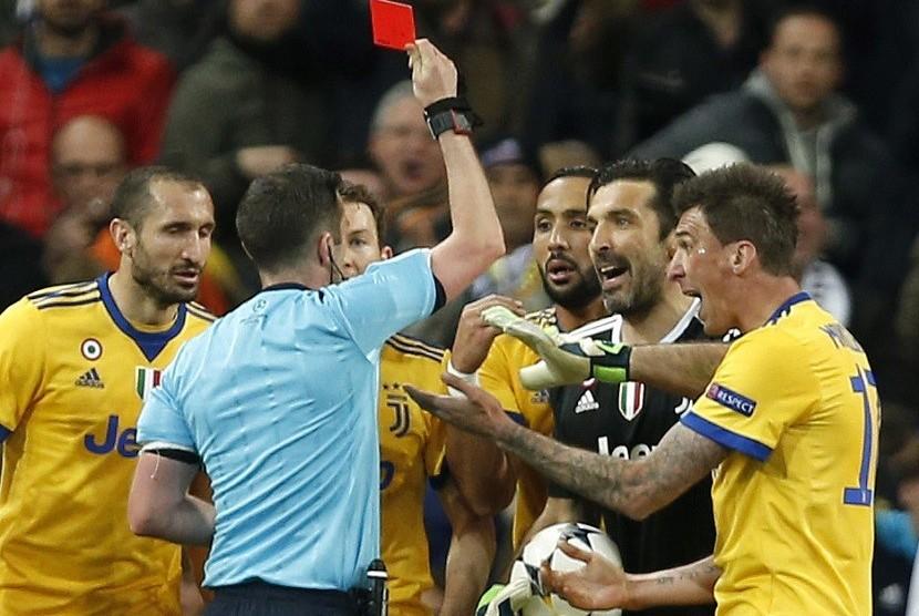 Wasit asal Inggris Michael Oliver memberikan kartu merah kepada kiper Juventus Gianluigi Buffin dalam perempat final leg kedua Liga Champions antara Real Madrid menghadapi Juventus di Santiago Bernabeu, Kamis (12/4) dini hari WIB.