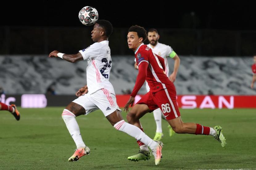 Winger Real Madrid Vinicius Jr membawa bola melewati pertahanan Liverpool.