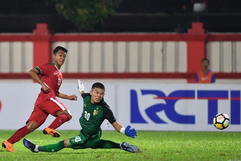 Winger timnas Indonesia U-23 Febri Hariyadi (kiri) menendang bola melewati penjaga gawang Thailand U-23 Kwanchai Suklom dalam pertandingan uji coba di Stadion PTIK, Jakarta, Kamis (31/5) malam.