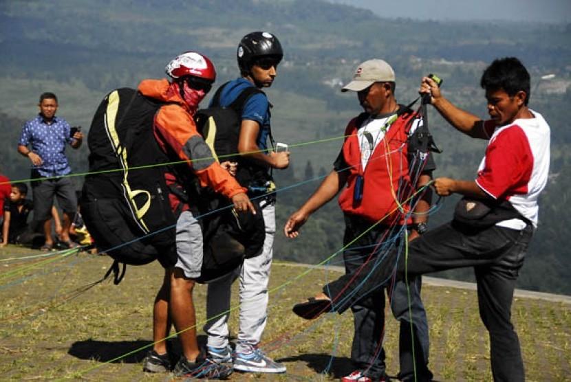 Wisatawan asal Timur Tengah (2 kiri) mendapat penjelasan sebelum melakukan penerbangan tandem bersama atlit paralayang di Puncak, Bogor, Jabar, Sabtu (2/8).