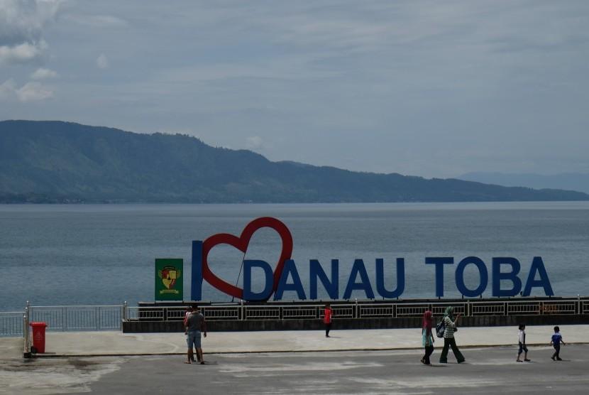 Wisatawan berada di kawasan Pantai Bebas Danau Toba, Parapat, Simalungun, Sumatera Utara, Jumat (27/10). Pemerintah