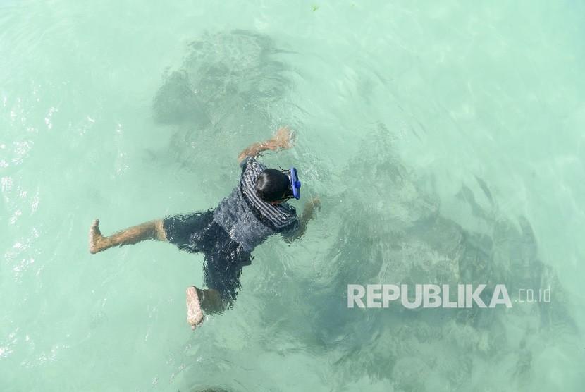 Wisatawan berenang di Pantai Jikumerasa di Pulau Buru, Maluku, Senin (15/4/2019).