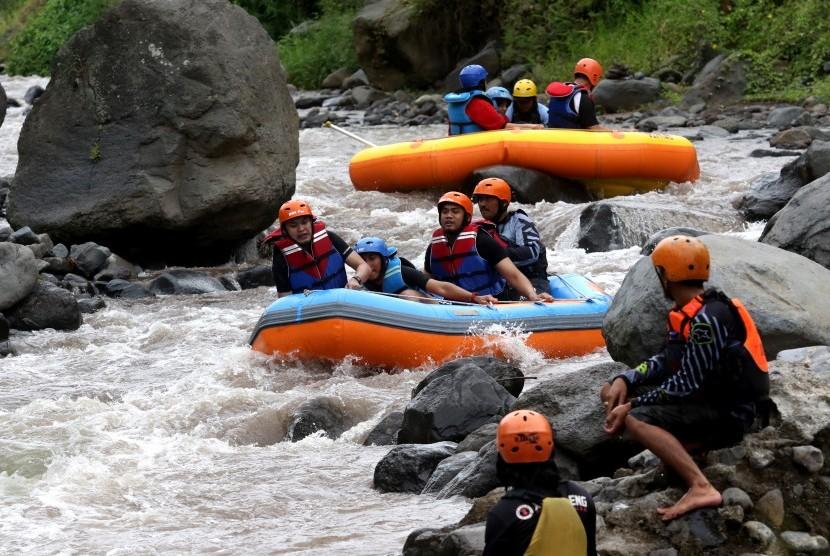 Wisatawan berpetualang arung jeram mengarungi sungai X Badeng di Songgon, Banyuwangi,Jawa Timur, Jumat (8/2/2019).