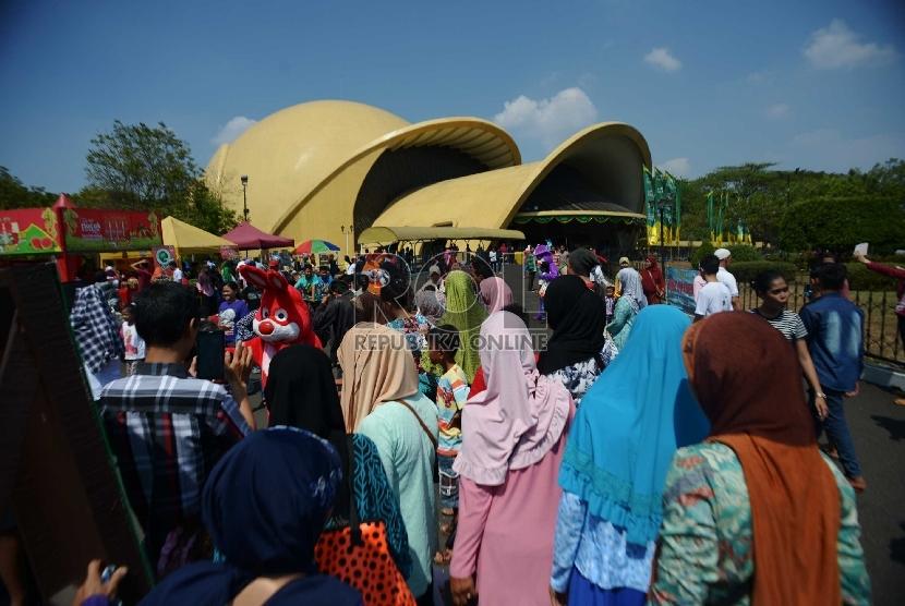 Wisatawan lokal memadati pelataran Teater Keong Emas Taman Mini Indonesia Indah (TMII), Jakarta, Ahad (19/7). Musim libur Lebaran seringkali dijadikan momentum bagi setiap keluarga untuk berkumpul, bersilaturahmi, serta berlibur bersama disejumlah tempat-t