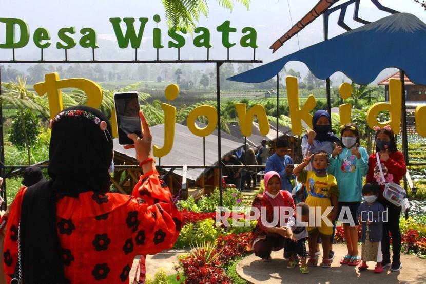 Wisatawan melakukan swafoto saat berekreasi di Desa Wisata Pujon Kidul, Malang, Jawa Timur, Rabu (26/5/2021). Sebagian masyarakat memanfaatkan libur saat Hari Raya Waisak dengan berekreasi di desa wisata tersebut karena mudah dijangkau dan relatif murah.