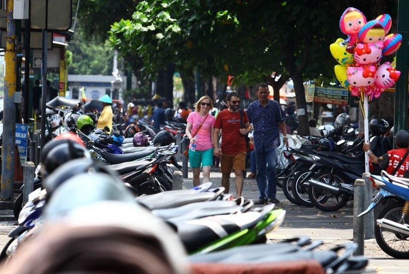 Wisatawan melintasi pedestrian di dekat lahan parkir sisi timur Jl Malioboro, DI Yogyakarta, Selasa (22/3).