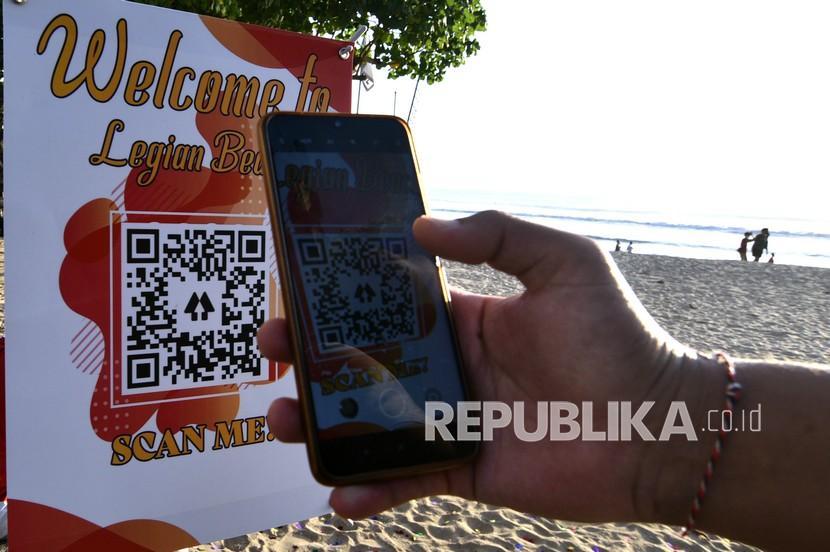 Pariwisata Bali Siap Buka untuk Turis Asing Oktober 2021. Wisatawan memindai QR Code saat akan memasuki kawasan wisata Pantai Legian, Badung, Bali, Sabtu (18/9/2021). Pengelola pantai tersebut mengembangkan dan meluncurkan sistem QR Code yang memudahkan wisatawan dalam mengakses aplikasi PeduliLindungi sebagai upaya mewujudkan destinasi pariwisata yang aman selama masa pandemi COVID-19.