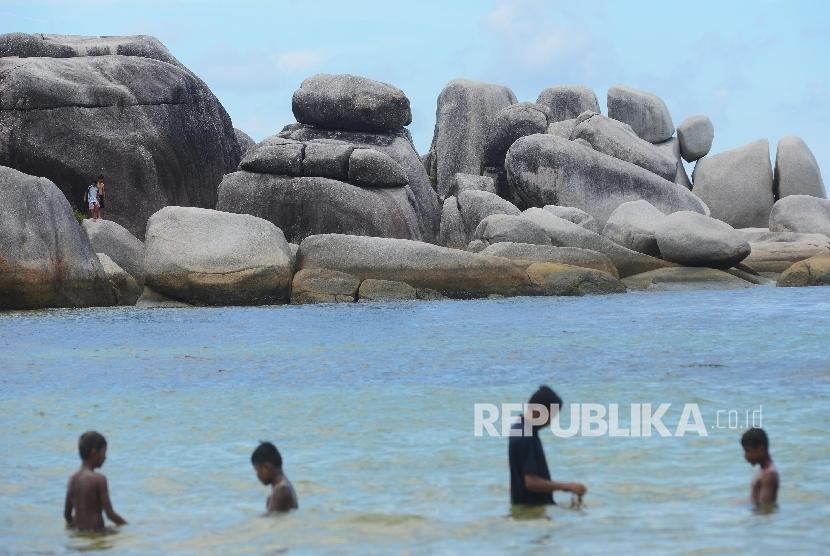 Wisatawan menikmati keindahan di Pantai Tanjung Tinggi, Belitung, Kamis (10/3).  (Republika/Raisan Al Farisi)