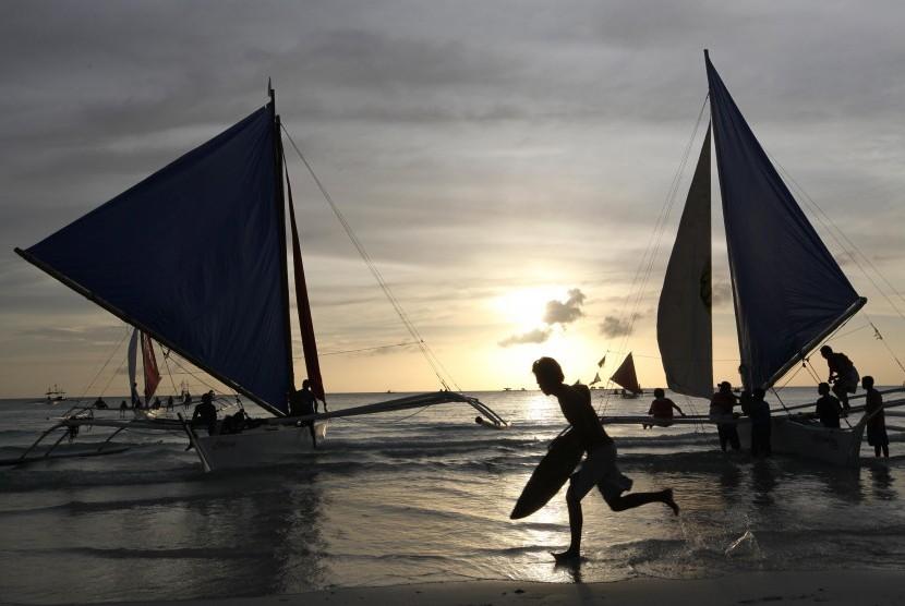 Wisatawan menikmati senja di Pantai Boracay, Filipina.