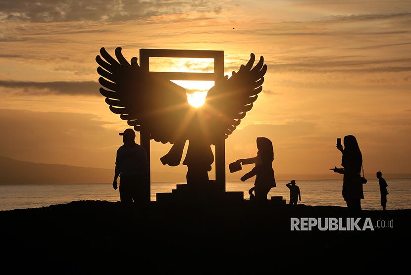 Wisatawan menikmati suasana matahari terbit pertama kali tahun 2018 di Pantai Boom, Banyuwangi, Jawa Timur, Senin (1/1).