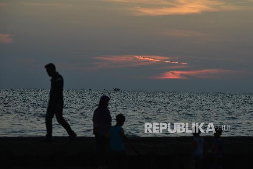 Wisatawan menikmati wisata Pantai Widuri, Pemalang, Jawa Tengah, Senin (25/5).