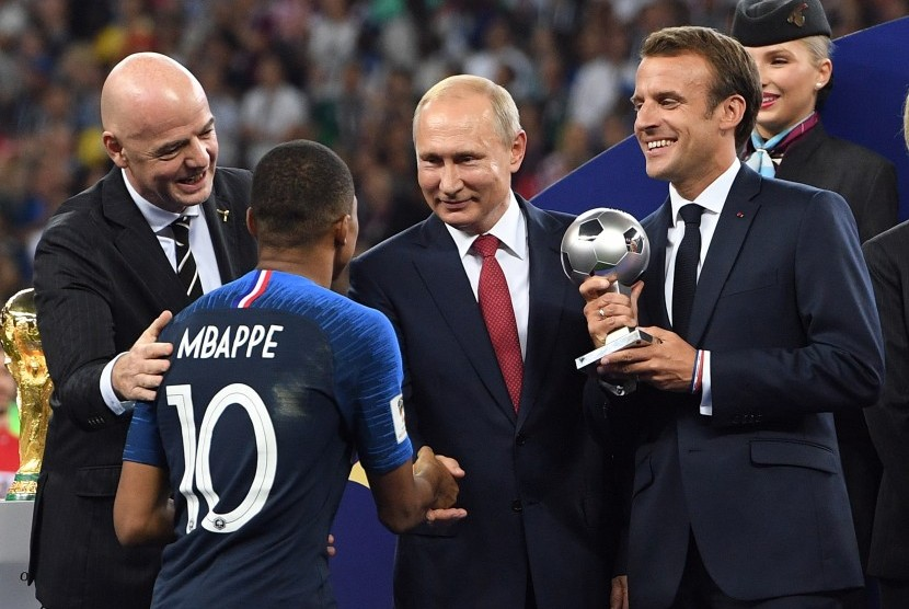 Kylian Mbappe berjabat tangan dengan Presiden Rusia Vladimir Putin (kedua dari kanan) sebelum menerima penghargaan sebagai pemain muda terbaik pada Piala Dunia 2018 dari Presiden Prancis Emmanuel Macron (kanan).