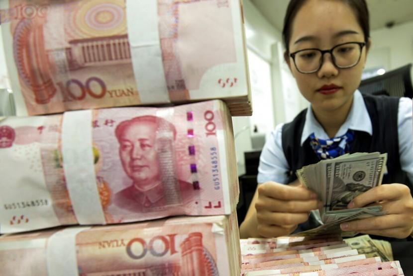 YUAN. Petugas bank menghitung dolar AS di samping tumpukan yuan Cina di Hai'an, Provinsi Jiangsu, China, Selasa (6/8). Nilai tukar yuan Cina merosot tajam atas dolar AS sebagai akibat dari perang dagang dengan Amerika Serikat.