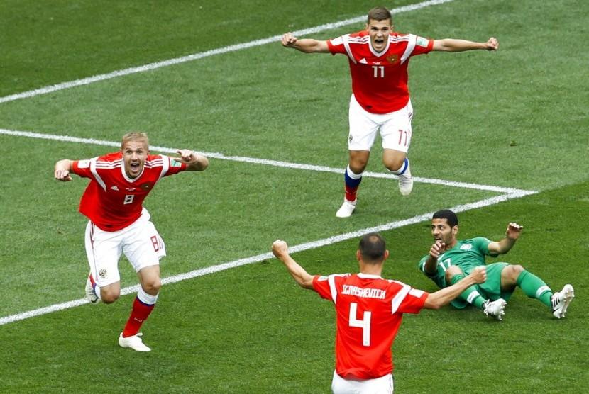 Yury Gazinsky (kiri) merayakan gol yang dicetaknya ke gawang Arab Saudi dalam laga pembuka Piala Dunia 2018 di Stadion Luzhniki, Moskow, Kamis (14/6).