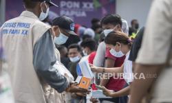 Satgas Prokes membagikan masker kepada warga yang mengantre untuk masuk menyaksikan pertandingan cabang olahraga futsal PON XX Papua di Gor SP 2, Kabupaten Mimika, Jumat (1/10/2021).
