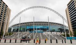 Seorang pekerja konstruksi berjalan di depan Stadion Wembley menjelang turnamen sepak bola UEFA EURO 2020 di London, Inggris, 11 Juni 2021.