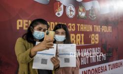 Sejumlah warga berfoto usai disuntik vaksin Covid-19 saat kegiatan vaksinasi Covid-19 masal di Aula BRSPDSN Wyata Guna, Jalan Pajajaran, Kota Bandung, Rabu (13/10). Pemerintah Provinsi Jawa Barat terus berupaya menggiatkan vaksinasi Covid-19 untuk mengejar target herd immunity atau kekebalan kelompok sebanyak 32 juta jiwa pada Desember 2021.