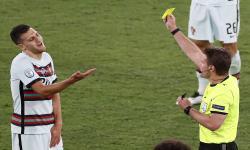 Diogo Dalot (kiri) dari Portugal mendapat kartu kuning dari wasit Jerman Felix Brych (kanan) pada pertandingan sepak bola babak 16 besar UEFA EURO 2020 antara Belgia dan Portugal di Seville, Spanyol, 27 Juni 2021.