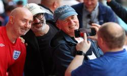 Komedian dan aktor Inggris Frank Skinner (kanan) dan komedian dan novelis Inggris David Baddiel (kedua dari kiri) berfoto dengan para penggemar sebelum dimulainya semifinal UEFA EURO 2020 antara Inggris dan Denmark di London, Inggris, 7 Juli.