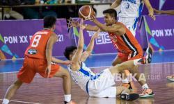 Pebasket putra Sulawesi Utara Luis Jovan Golung (kanan) berebut bola dengan pebasket putra Bangka Belitung Antoni Erga (tengah) saat bertanding pada pertandingan Basket Putra 5x5 PON XX Papua di Mimika Sport Complex, Papua, Rabu (29/9/2021).