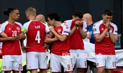 Pemain Denmark membuat tembok di sekitar rekan setimnya Christian Eriksen yang dibantu oleh petugas medis saat pertandingan grup B kejuaraan sepak bola Euro 2020 antara Denmark dan Finlandia di Parken Stadium di Kopenhagen, Sabtu (12/6).