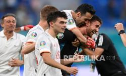 Penjaga gawang Spanyol Unai Simon melakukan selebrasi bersama rekan setimnya setelah menggagalkan tendangan penalti pada pertandingan perempat final kejuaraan sepak bola Euro 2020 antara Swiss dan Spanyol, di stadion Saint Petersburg di Saint Petersburg, Jumat (2/7).