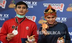 Pesilat Jawa Barat Asep Yuldan Sani (kanan) bersama pesilat DKI Jakarta Sugianto (kiri) memperlihatkan medalinya saat penyerahan medali Pencak Silat kategori Seni Tunggal Putra PON Papua di Gor Toware, Kabupaten Jayapura, Papua, Senin (11/10/2021). Pesilat Jawa Barat Asep Yuldan Sani berhasil meraih medali emas dengan poin 467 sedangkan medali perak diraih pesilat DKI Jakarta Sugianto dengan poin 461, dan perunggu diperoleh pesilat Papua Deryalfi Fathudin dengan poin 457.