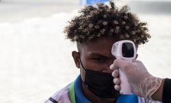 Petugas memeriksa suhu tubuh warga sebelum melakukan vaksinasi ditengah pelaksaan PON Papua di halaman Stadion Akuatik, Kampung Harapan, Kabupaten Jayapura, Papua, Selasa (28/9/2021). Vaksinasi yang di gelar di empat klaster PON Papua merupakan langkah percepatan vaksinasi COVID-19 bagi warga atau pengunjung selama perhelatan PON di Papua.