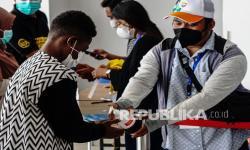 Petugas menyemprotkan cairan pembersih ke tangan seorang warga di pintu masuk lokasi pertandingan akuatik PON Papua, di Kampung Harapan, Kabupaten Jayapura, Papua, Jumat (24/9/2021). Panitia PON Papua menyediakan tiket gratis menonton pertandingan bagi warga yang telah divaksin COVID-19 dengan menerapkan protokol kesehatan.