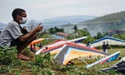Seorang bocah menonton pertandingan gantole nomor ketepatan mendarat PON Papua di Lapangan Advent, Doyo Baru, Kabupaten Jayapura, Papua, Jumat (24/9/2021).