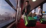 Para calon jamaah umrah menuju kabin pesawat Garuda Indonesia usai peresmian rute penerbangan langsung Surabaya-Jeddah di bandara Juanda, Surabaya, Ahad (13/4). (Republika/Rakhmawaty La'lang)