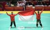 Pesilat Indoensia Yola Primadona Jampil dan Hendy membawa bendera merah putih usai final cabang pencak silat kelas artistik ganda putra Asian Games 2018 di Padepokan Pencak Silat TMII, Jakarta, Senin (27/8).