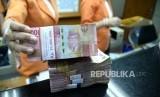 Transaksi Mata Uang Lokal. Petugas menghitung mata uang Rupiah di jasa penukaran uang, Jakarta, Senin (11/12).