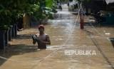 Warga beraktivitas ketika banjir melanda permukiman penduduk di Kawasan Pejaten Timur, Jakarta, Jumat (26/4).
