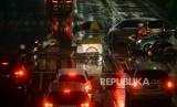 Pedagang menyeberangi pelican crossing menggunakan payung saat hujan di Jakarta, Selasa (27/11).