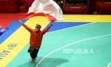 Pesilat Indoensia Puspa Arumsari berlari dengan membawa bendera merah putih usai beraksi pada final cabang pencak silat kelas artistik tunggal putri Asian Games 2018 di Padepokan Pencak Silat TMII, Jakarta, Senin (27/8).
