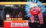 Warga menyaksikan dari bus Transjakarta saat parade Festival Jakarnaval 2018 yang melintas di Jalan Medan Merdeka Barat, Jakarta.