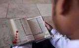 Seorang pelajar membaca Alquran seusai salat Jumat di Masjid Istiqlal, Jakarta, Jumat (31/8).