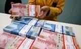 Karyawan menunjukan uang rupiah pecahan 100 ribu dan 50 ribu di Plaza Mandiri, Jakarta, Senin (23/9/2019).