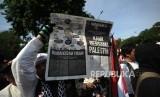 Peserta Aksi. Peserta aksi membentangkan koran Harian Republika  dalam  aksi damai di depan kantor Kedutaan Amerika Sertikat, Jakarta, Jumat (08/12).