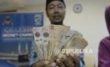 Calon jamaah haji memperlihatkan mata uang Saudi Riyal di Asrama Haji Pondok Gede, Jakarta, Rabu (17/7).