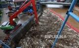 Petugas Dinas Lingkungan Hidup Pemprov DKI Jakarta mengoperasikan alat berat mengangkut sampah yang menumpuk di Pintu Air Manggarai, Jakarta, Ahad (8/4).