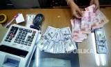 Petugas menghitung mata uang rupiah dan dolar AS di salah satu tempat penukaran uang di Jakarta. ilustrasi