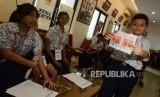 Sejumlah pelajar Sekolah Dasar Menteng 03 melakukan simulasi Pemilu di Indonesia saat berkunjung ke Gedung Komisi Pemilihan Umum (KPU), Jakarta, Selasa (6/11).