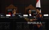 Komisioner KPU Hasyim Asyari saat akan memberikan barang bukti sampul surat suara sah dari pihak termohon pada sidang lanjutan Perselisihan Hasil Pemilihan Umum (PHPU) Pemilihan Presiden (Pilpres) 2019 di Gedung Mahkamah Konstitusi, Jakarta, Kamis (20/6).