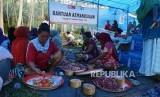 Ibu-ibu dan bapak-bapak pengungsi bergotong royong memotong-motong daging sapi dan memasak di dapur umum Posko Kemanusiaan ACT, di desa Lompio, Kabupaten Sirenja, Donggala Sulawesi Tengah, Ahad (14/10).